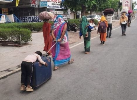 migrant-mother-boy-clinging-on-suitcase India